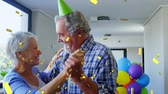 nascimento : Digital composite of an old Caucasian couple dancing at a birthday party while gold confetti fall in the screen Stock Footage