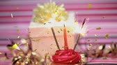 birth : Digital composite of a lighted candle and sparkles on a cupcake sparkling with a gift in the background and gold confetti falling
