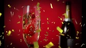 szampan : Digital composite of a glass of champagne with a strawberry and a bottle in the background while gold confetti fall in the screen