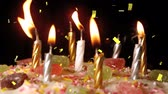 narodziny : Digital animation of lighted candles on a birthday cake while gold confetti falls Wideo