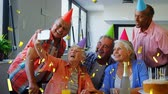 companheiro : Digital composite of a group of old diverse friends taking a picture with a cellphone while celebrating a birthday and wearing party hats. Gold confetti fall in the foreground.