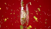 necklace : Digital composite of a glass of champagne with a pearl necklace against a red background while gold confetti fall in the screen