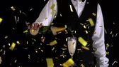 flauta : Digital composite of a Caucasian waiter pouring champagne in a glass while gold confetti fall in the screen.