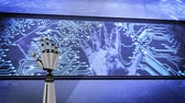 Animation of robot hand turning and clenching fist, in front of a large screen outdoors, with glowing computer circuit board and flashing hand on it, cloudy blue sky in the background