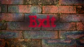 указывать : Animation of the word Exit in flickering red neon on a red brick wall