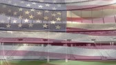 maç : Animation of a blowing American flag in front of a sports stadium Stok Video