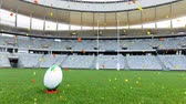 konfeti : Animation of a rugby ball at sports stadium with red and yellow confetti falling Stok Video