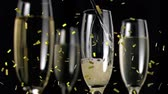 szampan : Animation of a close up of champagne being poured into a glass with three full glasses and golden confetti falling on a black background