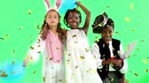 konijntje : Animation of multi-ethnic children at a party, a Caucasian girl in a bunny costume, an African American boy in a pirate costume, an African American girl with face paint on, playing with balloons, embracing and smiling to camera on green background, while