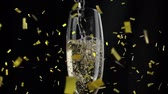 flauta : Animation of a close up of champagne being poured into a glass with golden confetti falling on a black background