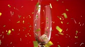 flauta : Animation of a close up of champagne being poured into a glass with golden confetti falling on a red background