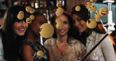 emoticon : Animation of emoji icons flying from right to left with a group of young multi-ethnic female friends taking a selfie with a selfie stick in a bar in the background 4k