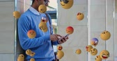 emoticon : Animation of emoji icons flying from right to left with a young mixed race man using a smartphone in the background 4k