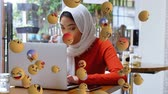 emoticon : Animation of emoji icons flying from left to right with a young mixed race woman wearing a hijab and using a laptop and a smartphone in the background