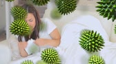 biologisch : Animation of green 3d viruses with an ill Caucasian woman coughing and blowing her nose in the background