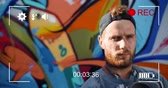 cronometragem : Animation of a portrait of a young Caucasian man in front of graffiti, seen on a screen of a digital camera in record mode with icons and timer 4k