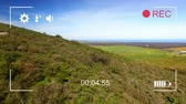 cronometragem : Animation of countryside, seen on a screen of a digital camera in record mode with icons and timer Stock Footage