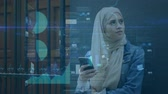 統計 : Animation of a young mixed race woman wearing a hijab and using a smartphone with data processing in the foreground