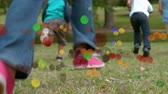 자유 시간 : Animation of coloured spots of defocused twinkling light passing in front of young children running away from camera across a garden