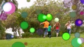 çevreler : Animation of coloured spots of defocused twinkling light passing in front of young children running away from camera across a garden