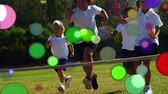 mudanza : Animation of coloured spots of defocused twinkling light passing in front of young children running in a field