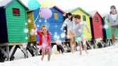mudanza : Animation of white spots of defocused twinkling light passing in front of a Caucasian couple with two young children running with balloons and playing on a beach
