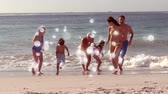 çevreler : Animation of white spots of defocused twinkling light passing in front of a three generation Caucasian family with two young children running and playing on a beach Stok Video