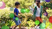 çevreler : Animation of coloured spots of defocused twinkling light passing in front of young boys playing football in a garden