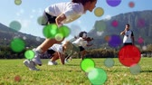 çevreler : Animation of coloured spots of defocused twinkling light passing in front of young children starting a race across a field Stok Video