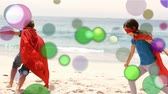przyjaźń : Animation of coloured spots of defocused twinkling light passing in front of two young Caucasian children wearing red capes and masks running and playing on a beach