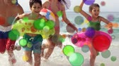 mami : Animation of coloured spots of defocused twinkling light passing in front of a Caucasian couple with two young children running and playing on a beach