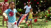 indépendance : Animation of red and white spots of defocused twinkling light passing in front of a mixed race family running with American flags in a garden