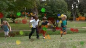 çevreler : Animation of coloured spots of defocused twinkling light passing in front of young children running to camera across a garden Stok Video