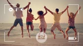 atlama : Animation of a rear view of a group of young multi-ethnic male and female friends holding hands and jumping on a beach, seen on a screen of a smartphone in picture mode with icons in the foreground Stok Video
