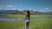 sportovní výstroj : Animation of a rear view of a young Caucasian woman practicing yoga in countryside, shutter opens and closes Dostupné videozáznamy