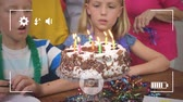 ミッド : Animation of a close up of pre teen Caucasian boy and girl blowing out candles on a birthday cake, seen on a screen of a smartphone in picture mode with icons in the foreground