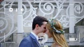 husband : Animation of a side view of a young Caucasian bride and groom kissing, seen on a screen of a smartphone in picture mode with icons in the foreground