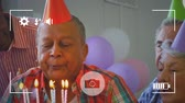 freundlichkeit : Animation of a close up of senior mixed race man blowing out candles on a birthday cake with a group of friends behind him, seen on a screen of a smartphone in picture mode with icons in the foreground