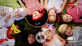 volet : Animation of a overhead view of a group of multi-ethnic children in fancy dress costumes lying on a grass, seen on a screen of a smartphone in picture mode with icons in the foreground
