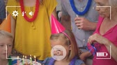 ミッド : Animation of a close up of a three generation Caucasian family with a pre teen boy and girl blowing out candles on a birthday cake, seen on a screen of a smartphone in picture mode with icons in the f