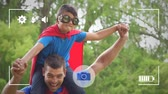 родитель : Animation of a Caucasian man carrying his pre teen son in a red cape and a mask piggyback in a garden, seen on a screen of a smartphone in picture mode with icons in the foreground Стоковые видеозаписи