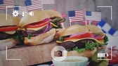 indépendance : Animation of a close up of hamburgers with American flags, seen on a screen of a smartphone in picture mode with icons in the foreground Vidéos Libres De Droits