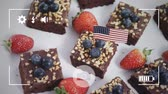 tatarak : Animation of a close up of brownie cakes with strawberries and blueberries with American flags, seen on a screen of a smartphone in picture mode with icons in the foreground Wideo