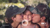 ミッド : Animation of a portrait of a young Caucasian male and female soldier kissing their young daughter on cheeks, seen on a screen of a smartphone in picture mode with icons in the foreground