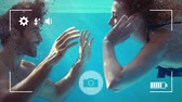 mulheres adultas meados : Animation of a side view close up of a young Caucasian man and woman holding hands under water, seen on a screen of a smartphone in picture mode with icons in the foreground