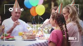 mami : Animation of a three generation Caucasian family at a birthday party sitting at a table in a garden, using party blowers, seen on a screen of a smartphone in picture mode with icons in the foreground Archivo de Video