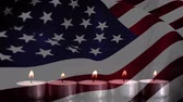 dördüncü : Animation of a row of lit candles burning with a US flag billowing in the background