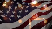 respeito : Animation of lit candles burning with a US flag billowing in the background