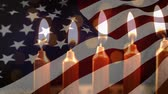 gwiazda : Animation of lit candles burning and flickering lights with a US flag billowing in the background