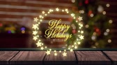 oslava : Animation of the words Happy Holidays in yellow letters in a round frame of glowing star shaped fairy lights with Christmas tree in the background